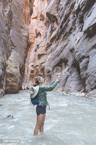 Solo female hiker wades through a majestic red rock canyon in Utah. She is alone, but there is a group hiking ahead of her in the background. Just the canyon and mountains ahead of her. She has stopped to take a selfie.