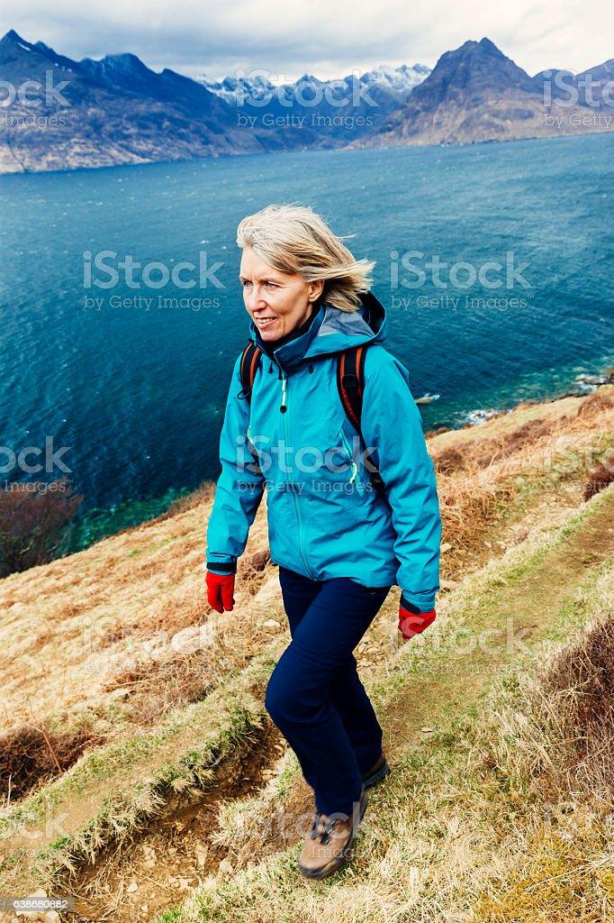 Female hiker walking on coastal trail, Skye. AdobeRGB stock photo
