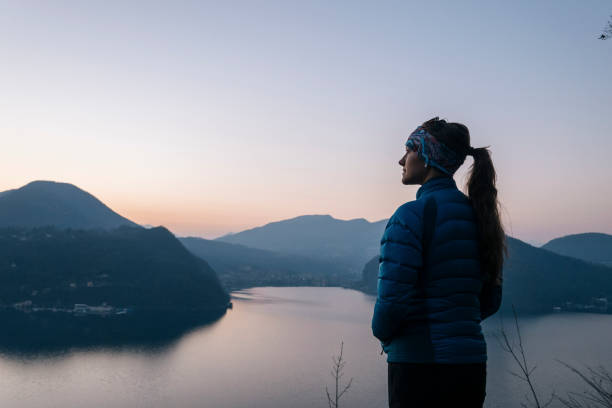 Female hiker walks above lake and European alps stock photo