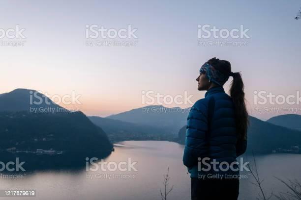 Photo of Female hiker walks above lake and European alps