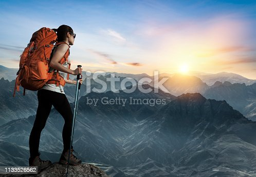 Female hiker watching sunset on top of the mountain peak