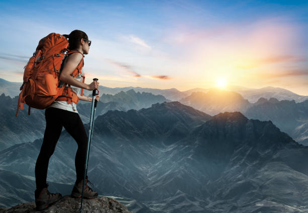 Female hiker watching sunset on top of the mountain peak stock photo