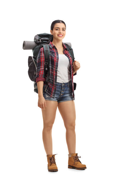 Female hiker with backpack standing and looking at the camera stock photo
