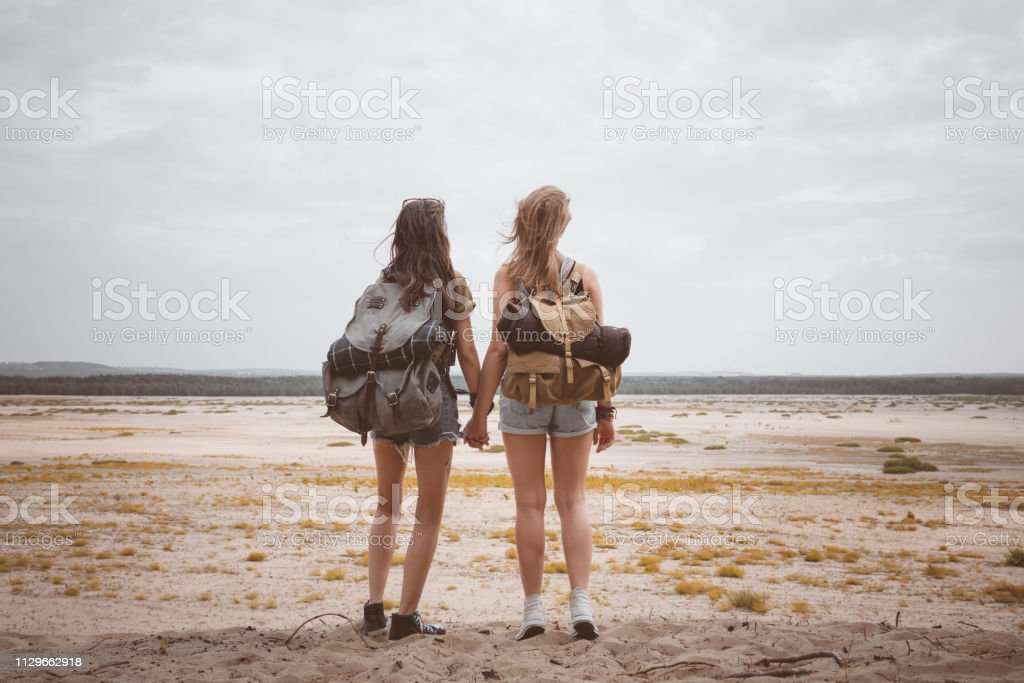 Female hikers holding hands in desert Rear view of female hikers holding hands in desert. Full length of young women are looking at landscape. They are standing with backpacks. 20-24 Years Stock Photo