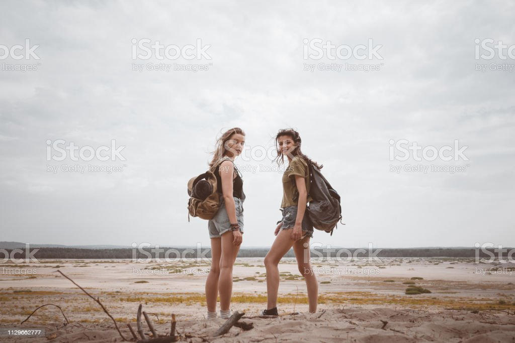 Female hikers standing in desert against sky Portrait of young women standing in desert. Full length of female hikers are with backpacks. They are spending summer vacation together. 20-24 Years Stock Photo