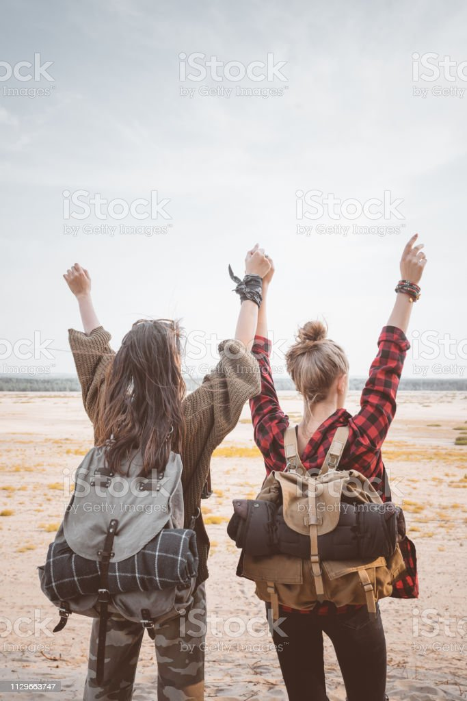 Female hikers standing with arms raised in desert Rear view of young women looking at landscape. Female hikers are holding hands in desert. They are standing with arms raised. 20-24 Years Stock Photo