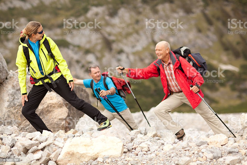 female hiking guide looking back to senior hiker stock photo