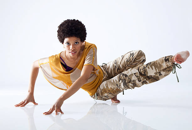 Female hip hop dancer mid move with all white background stock photo