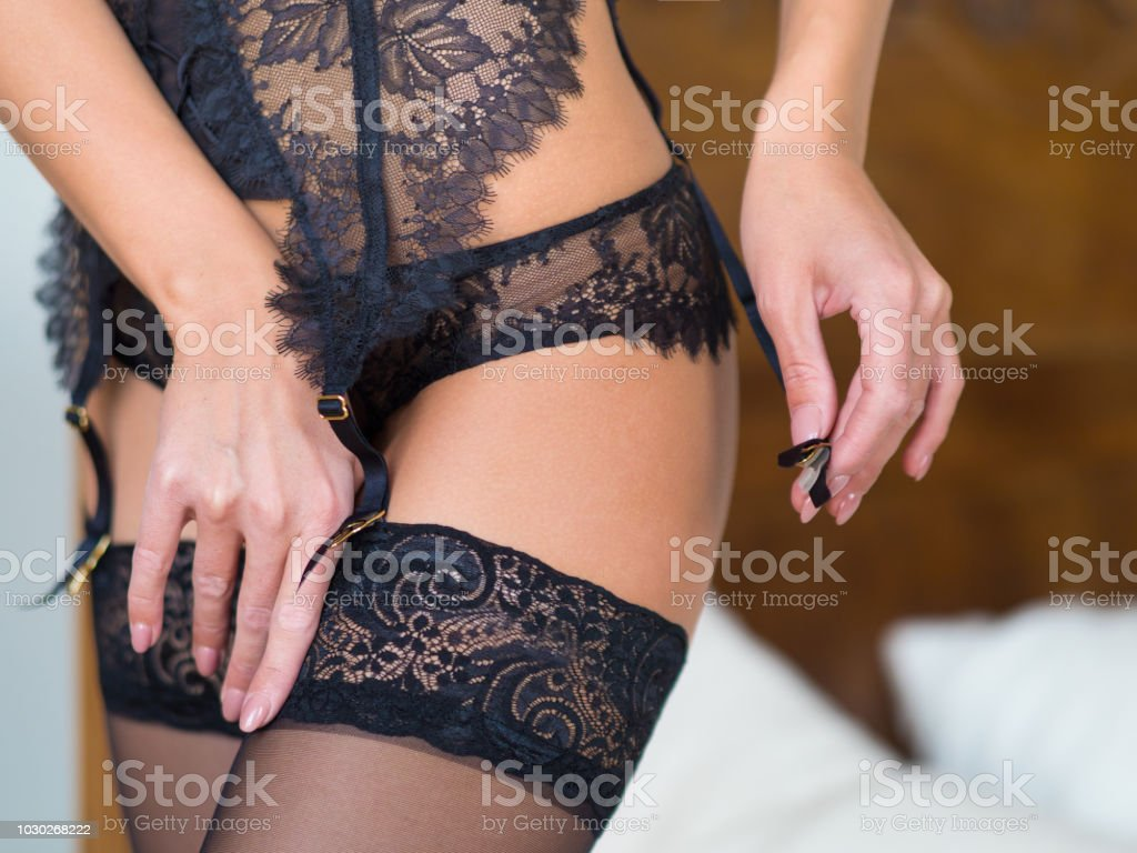 female hips in classical black stockings and garter belt in a bedroom interior stock photo