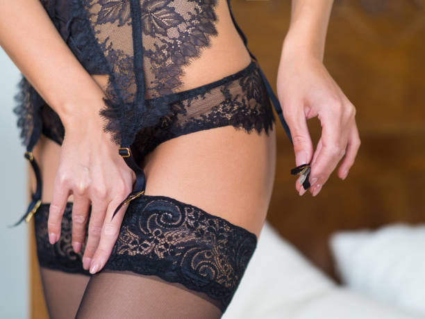 female hips in classical black stockings and garter belt in a bedroom interior female hips in classical black stockings and garter belt in a bedroom interior. lingerie stock pictures, royalty-free photos & images
