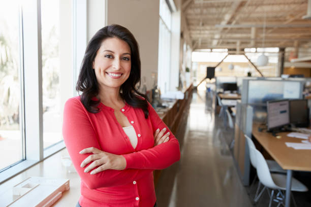 Female Hispanic architect smiling to camera in an office Female Hispanic architect smiling to camera in an office latin american and hispanic ethnicity stock pictures, royalty-free photos & images