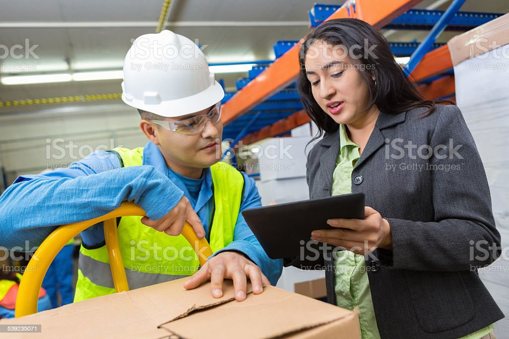 Female Hispanic warehouse manager using digital tablet with worker stock photo