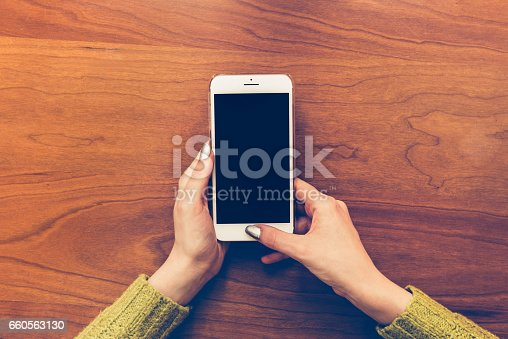 Female hold and touch screen on cell phone on wooden background.