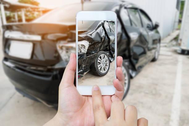 mujer mantenga móvil smartphone fotografiando a accidente de coche - foto de stock