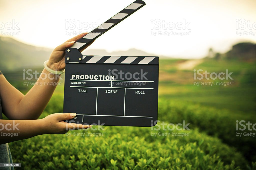 A female holding a clapper board while shooting outside royalty-free stock photo