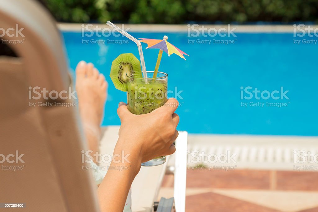 Female holding a glass of kiwi smoothie stock photo
