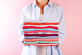 istock Female holding a pile of folded clothes, unisex for both man & woman, different color & material. Trip preparation concept. 961836574