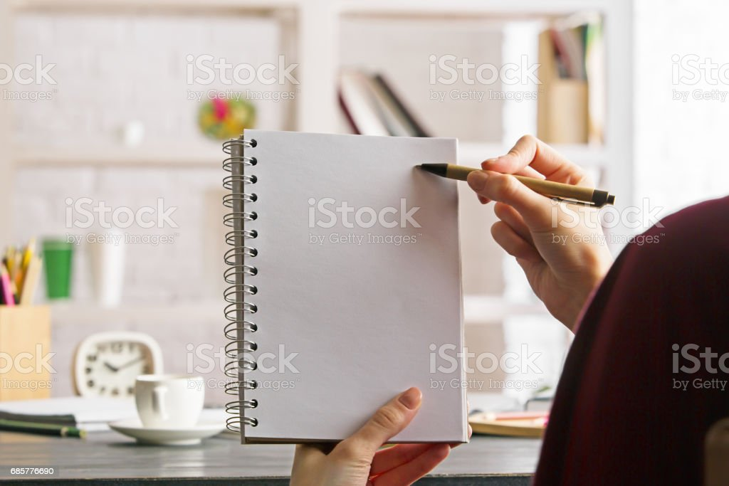 Female holding and writing in notepad royalty-free stock photo