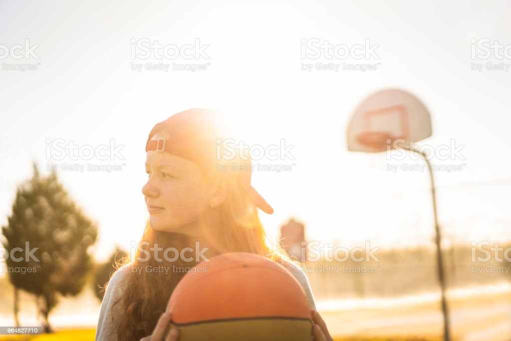Female holding basketball while looking away royalty-free stock photo