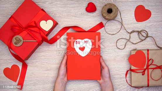 1125461272 istock photo Female holding greeting card with be my phrase, hand-made gift boxes on table 1125461260
