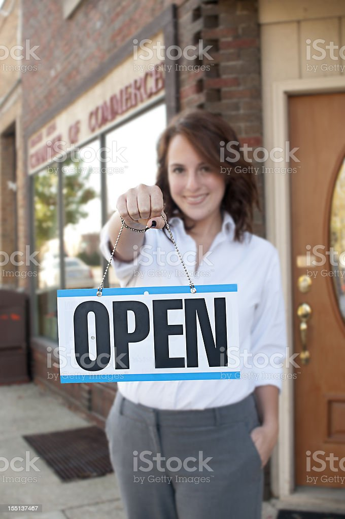 A female holding up a open for business sign royalty-free stock photo