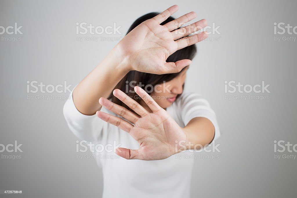 Female holds her hands up to prevent a picture of her face stock photo