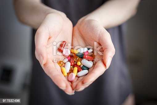 istock Female holds pills of different color in hand. Concept of health 917532496