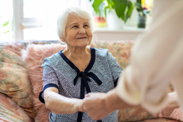 Female home carer supporting old woman to stand up from the sofa at care home stock photo