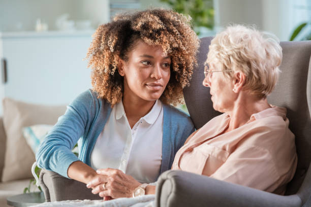 Female home carer talking with senior woman stock photo