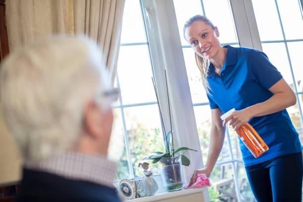 vrouw thuis help schoonmaak huis voor senior man - thuiszorg stockfoto's en -beelden