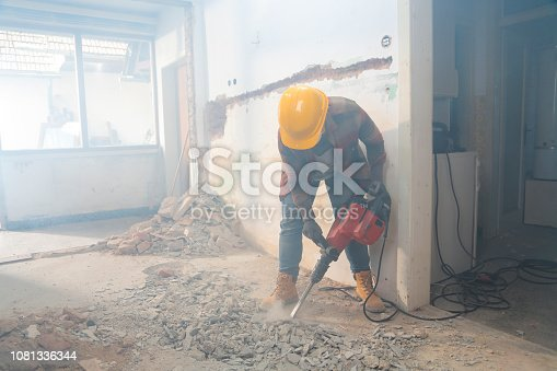 Woman with a drill machine making new flooring and wall instalations. Demolishing old first.