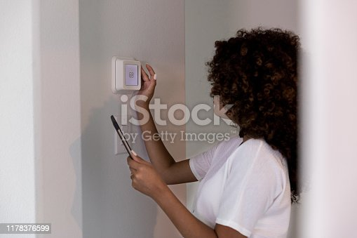Young woman uses mobile app to adjust or program her new home's temperature.