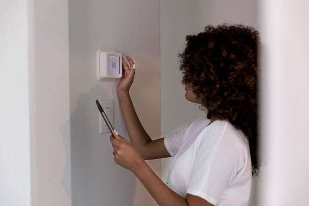 Female homeowner adjusts thermostat stock photo