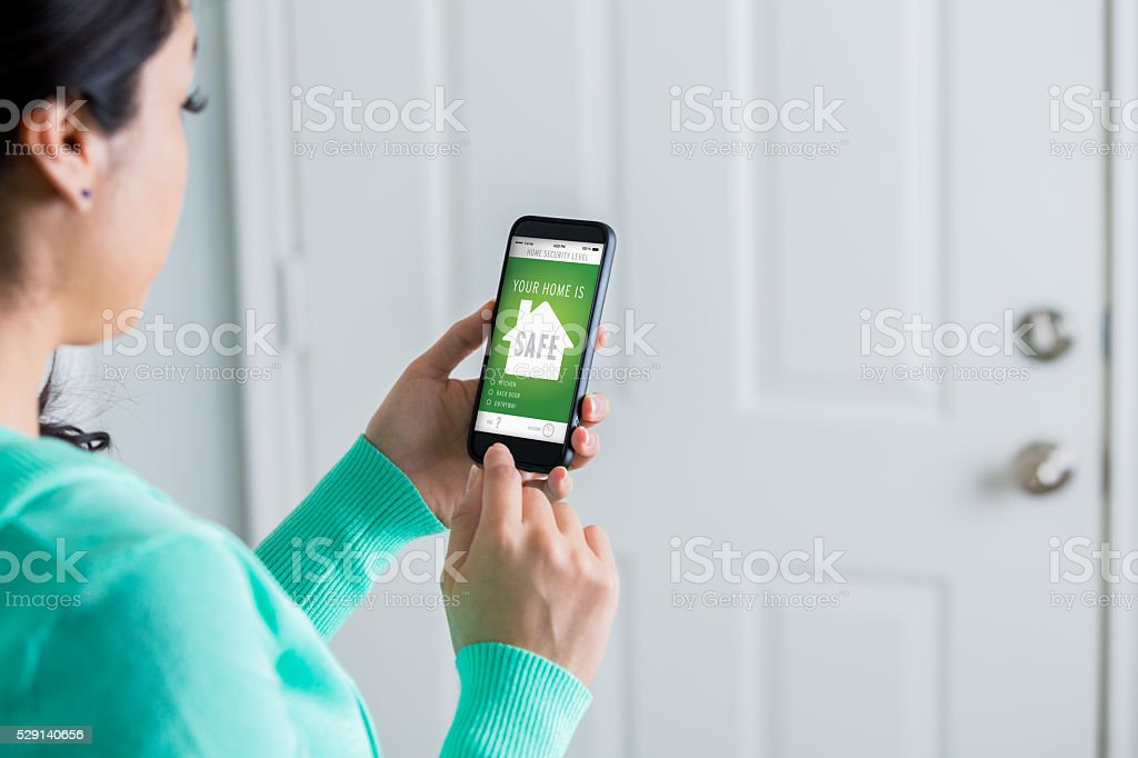 Female homeowner uses smart phone to check home security stock photo