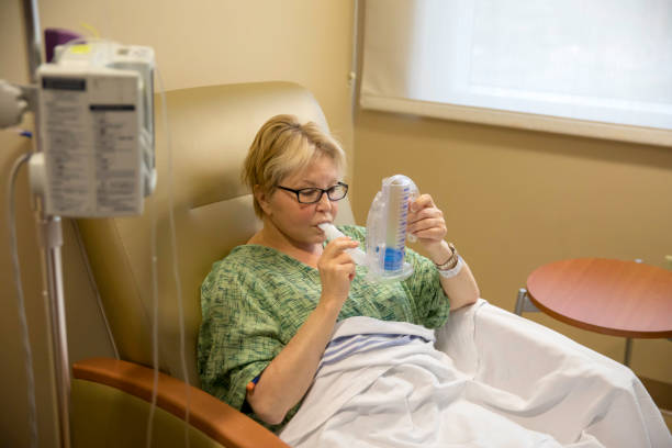 Female hospital patient doing breathing exercises with a spirometer stock photo