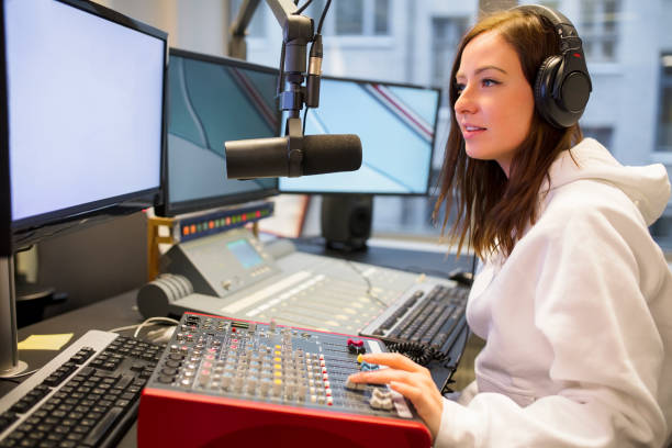 female host using control panel at radio station - radio dj stock photos and pictures
