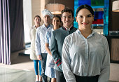 Female hotel manager and her team standing behind her all smiling at camera very happy
