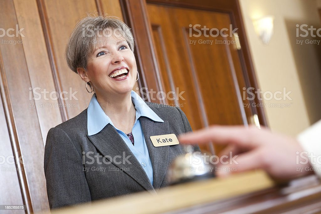 Female hotel manager behind a desk with guest ringing bell royalty-free stock photo
