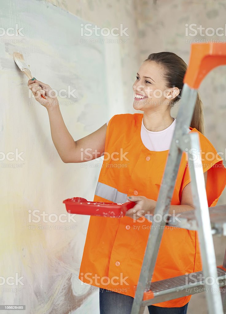 Female house painter paints wall stock photo