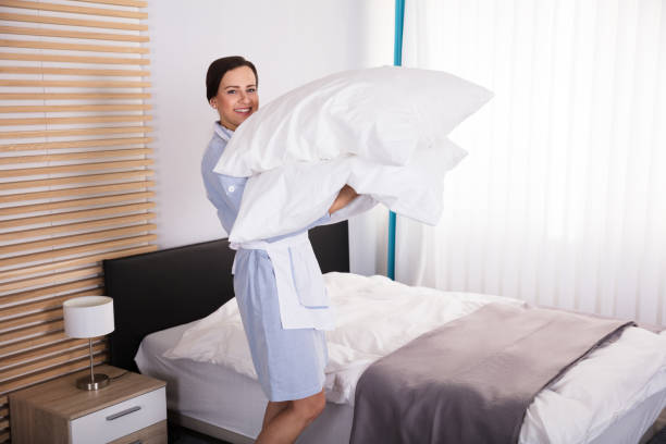 weibliche haushälterin mit kissen im hotelzimmer - verwandlungskissen stock-fotos und bilder