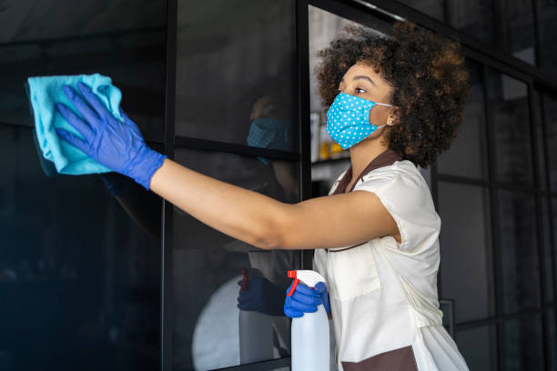 Female housekeeper cleaning mirror stock photo