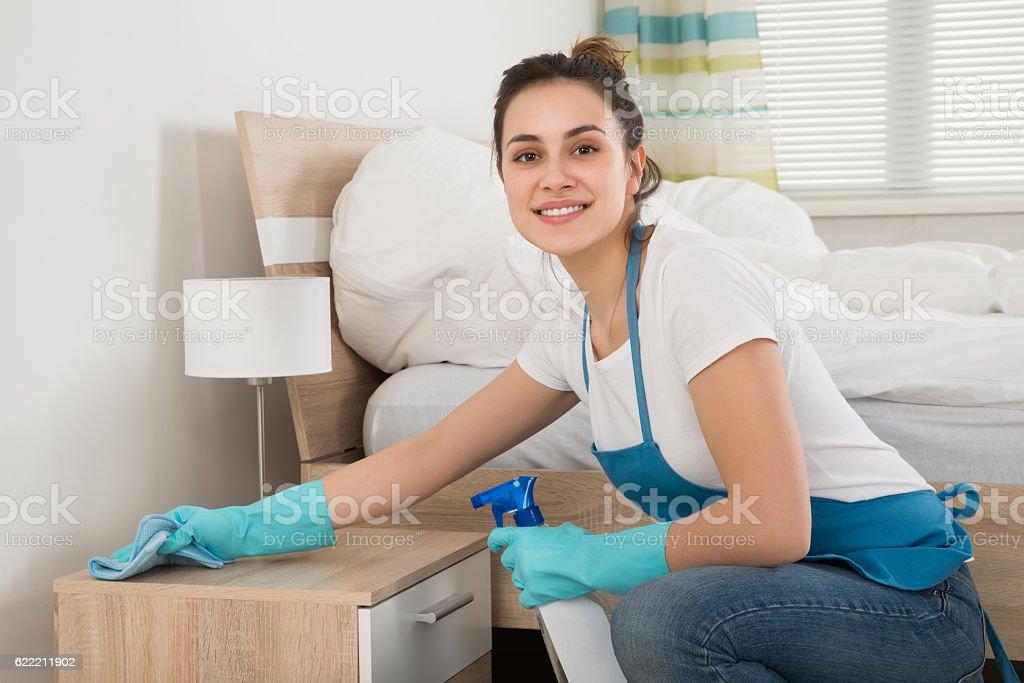 Female Housekeeper Cleaning Nightstand stock photo