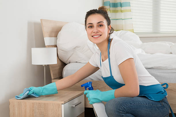 Female Housekeeper Cleaning Nightstand stock photo