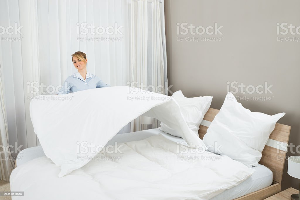 Female Housekeeping Worker Making Bed stock photo