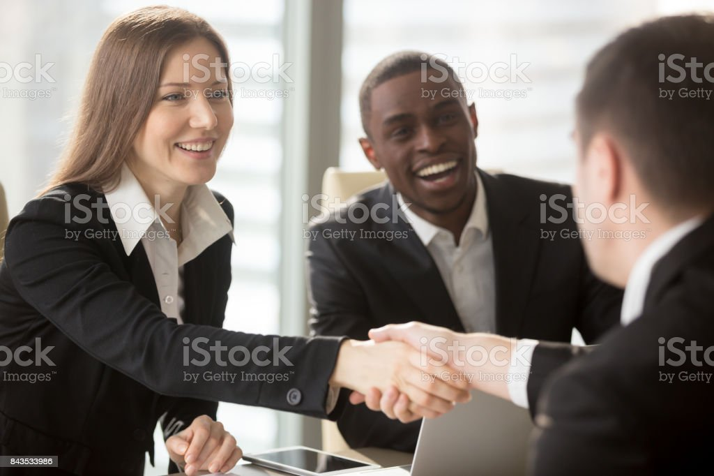 Female HR manager handshaking with job applicant stock photo