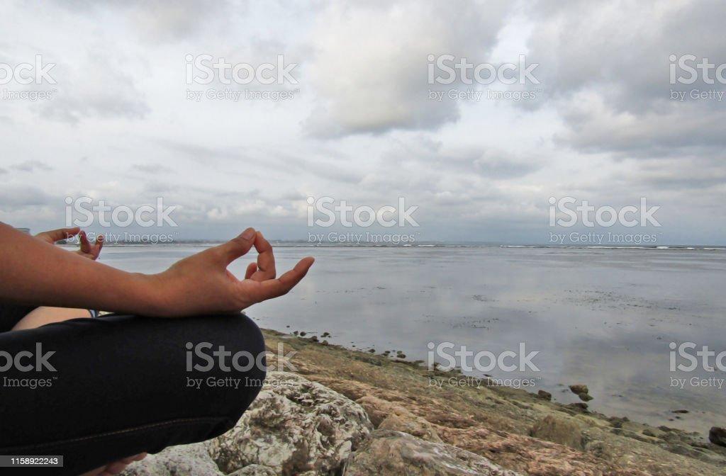 Meditation. Woman meditating, relaxing in yoga pose in the beach, zen...