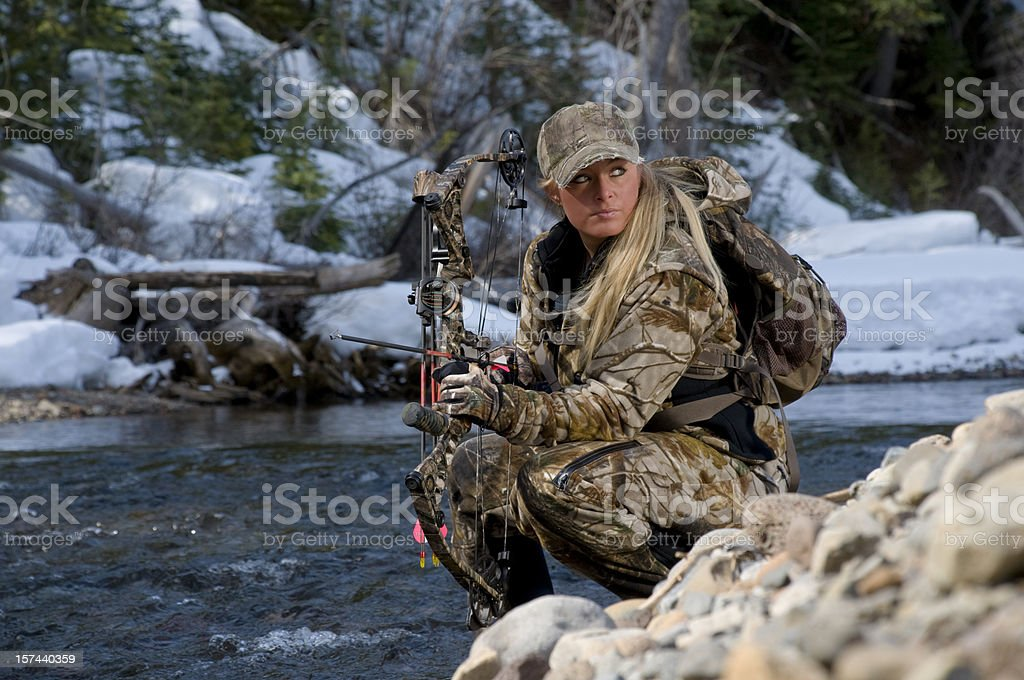 Female hunter kneeling by a pile of rocks stock photo