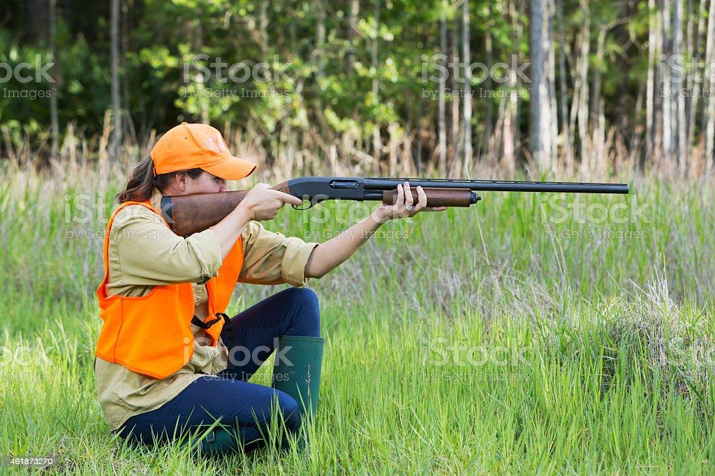 Female hunter with shotgun kneeling in tall grass stock photo