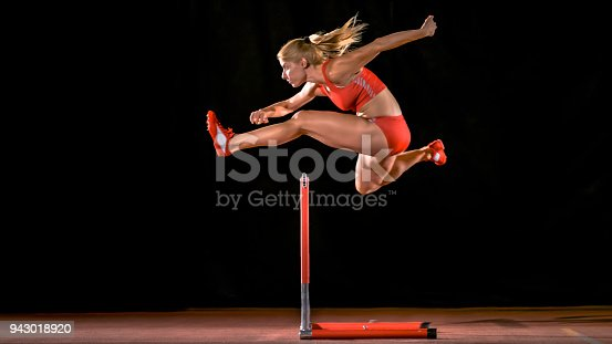 Female sprinter jumping over hurdle on track.