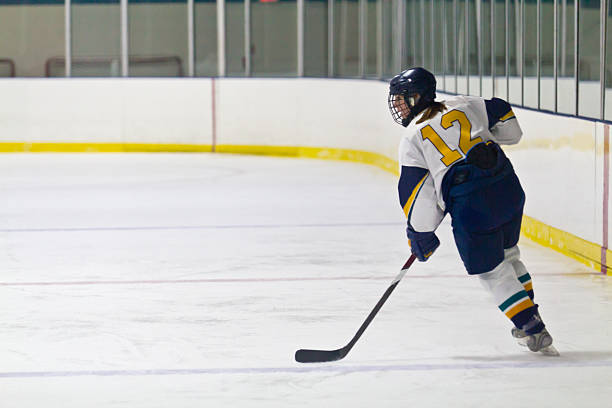 Female ice hockey player skating during a game stock photo